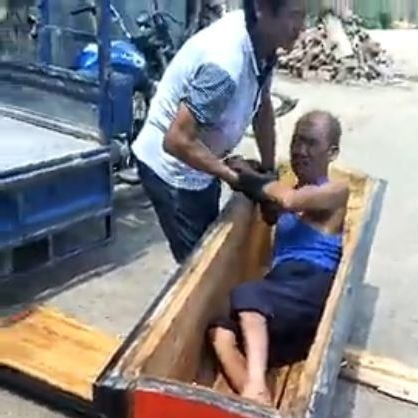 Still from a video showing a man in a coffin, and another man trying to pull him out.