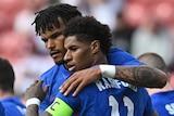 Marcus rashford celebrates by hugging teammates