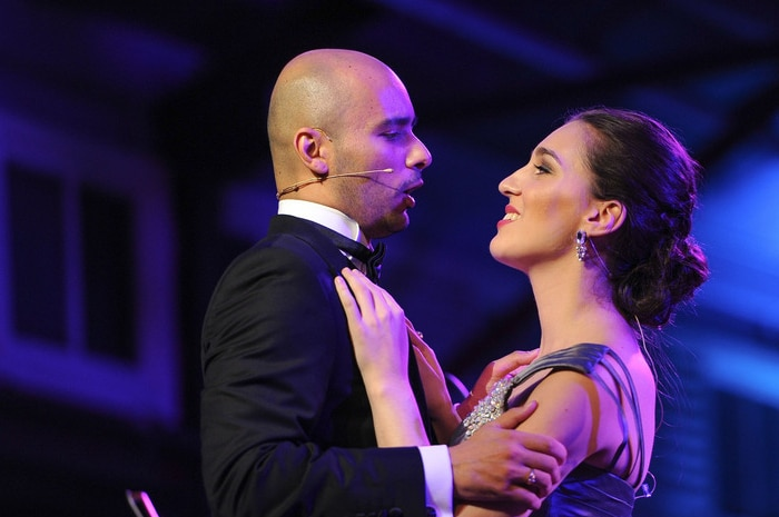 Man and women embrace on stage, singing