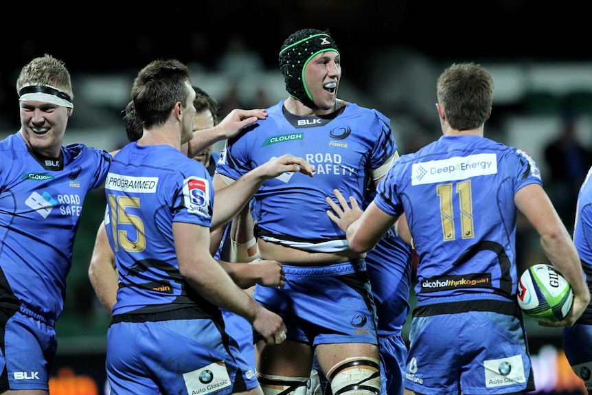A smiling Adam Coleman of the Western Force is congratulated by his teammates after scoring a try.