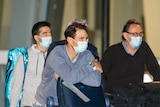 Rafael Nadal wears a mask and leans on a baggage carousel