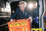 British PM Boris Johnson leans into the back of a cold drink delivery van, grabbing a crate full of juice bottles.