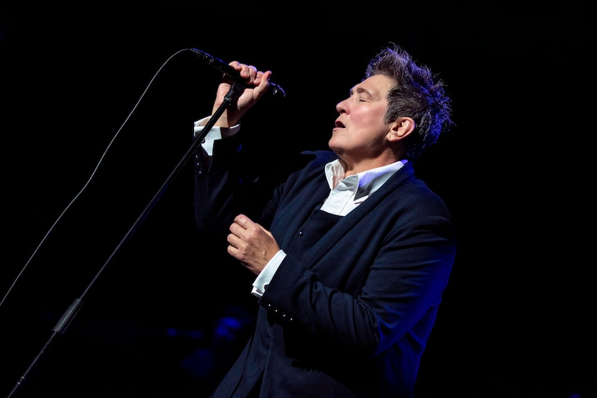 kd lang sings into a microphone, wearing a suit jacket. Black background.