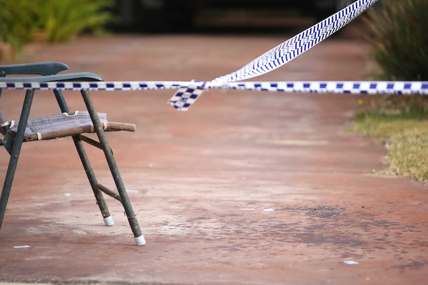 Police tape tied to a chair on a driveway with blood spatters out the front of a suburban house.