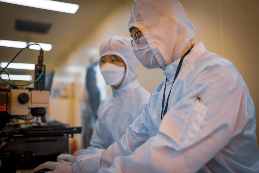 Two Koreans in full PPE examining factory equipment