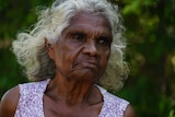 A medium close-up of an elderly Aboriginal woman, who is standing talking to a reporter but looking off camera.