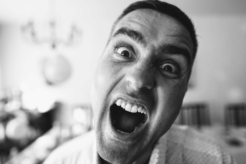 Black and white photo of close up of man's face with his mouth wide open.