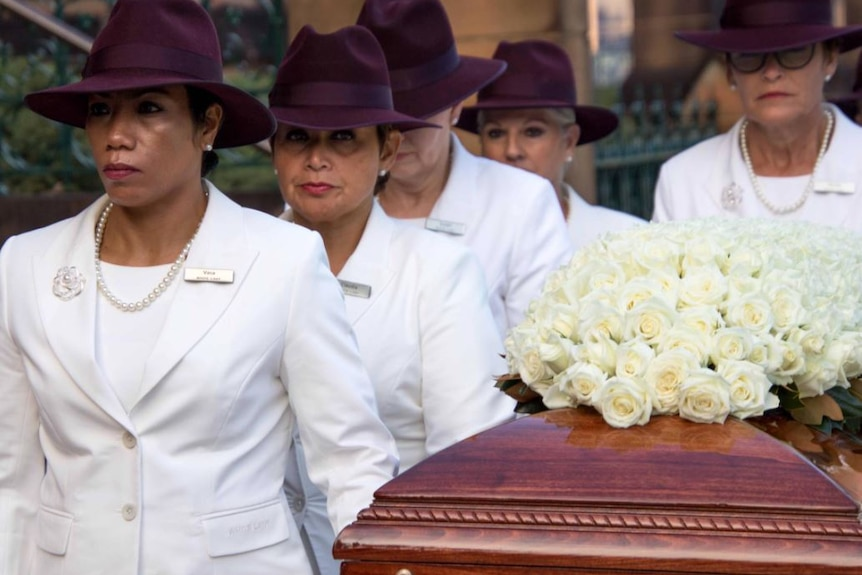Five women wearing white suits, pearls and maroon hats stand next to a coffin covered in white roses.