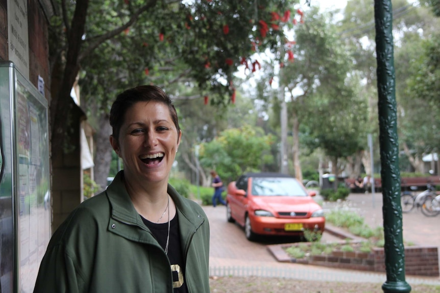 A woman laughs in front of a wattle tree and a parked car in the background.