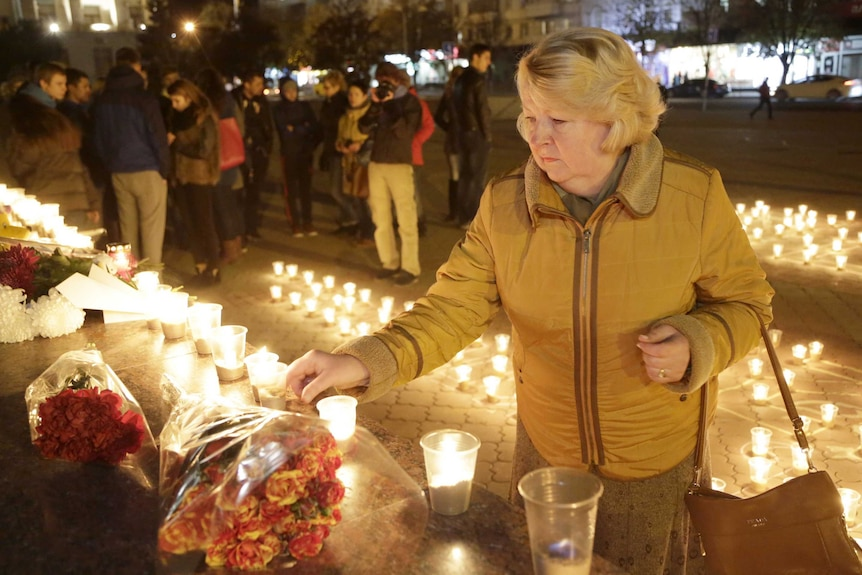 A woman lights a candle in honour of victims of a Russian airliner crash