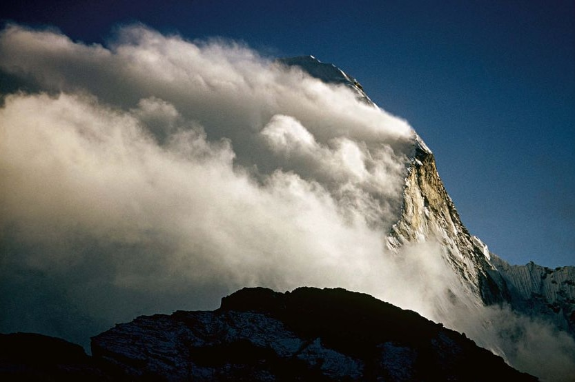 Clouds rush over a peak in the Himalayas