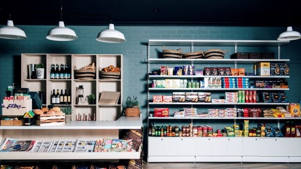 A small corner store with shelves stocked with products.