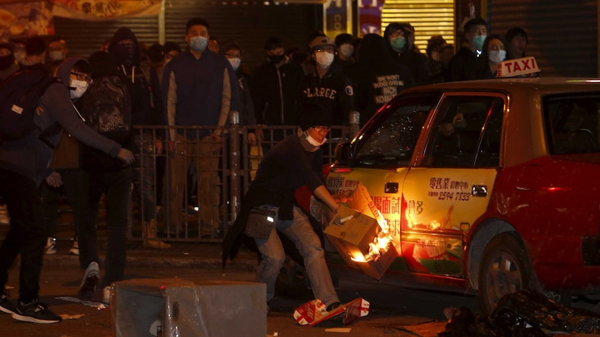 A protestor sets fire to a taxi during night time protests at Mongkok distrcit in Hong Kong
