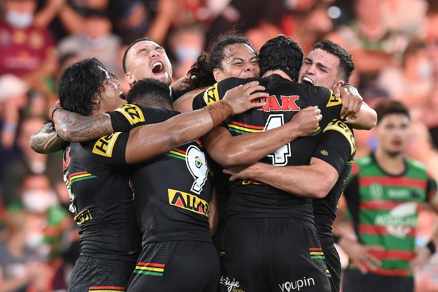 Rugby league players celebrate after winning the grand final
