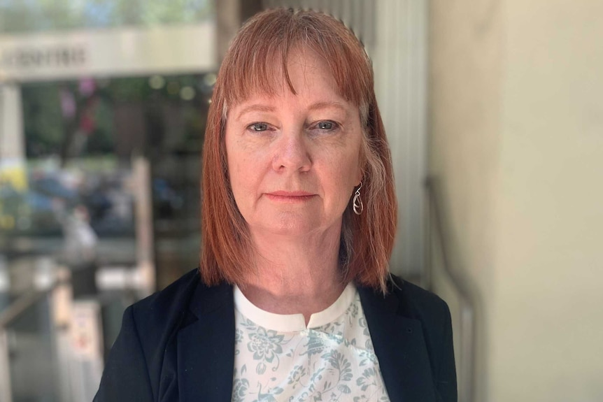 Woman with red hair looking into the camera.