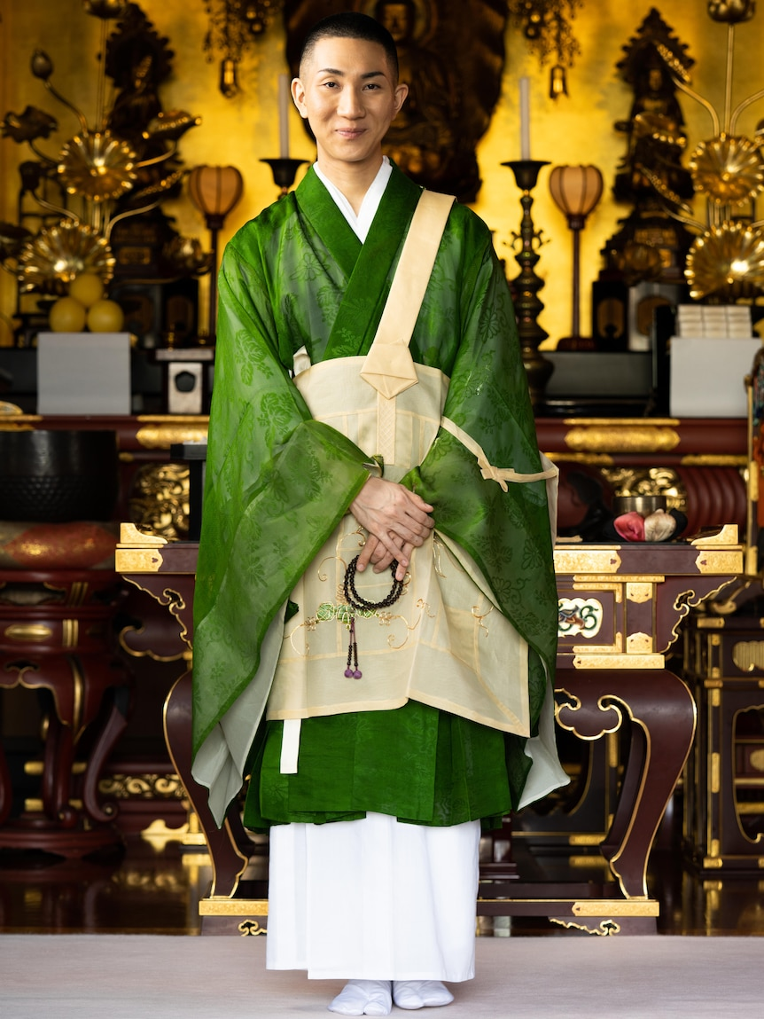 A Buddhist monk in a green gown, surrounded by gold artefacts with a slight smile on his face