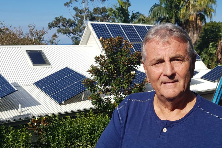Rex Leighton in front of his house, which has solar panels on the roof.