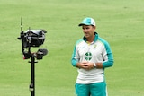 An Austrlaian cricket coach stares into a camera while giving a TV interview on the ground during a Test match.