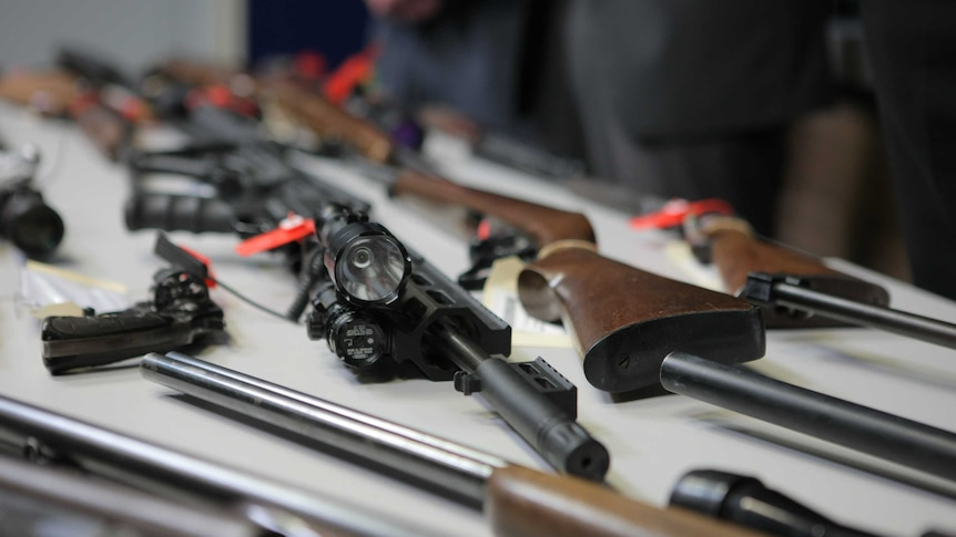 Several guns laid out on a table.