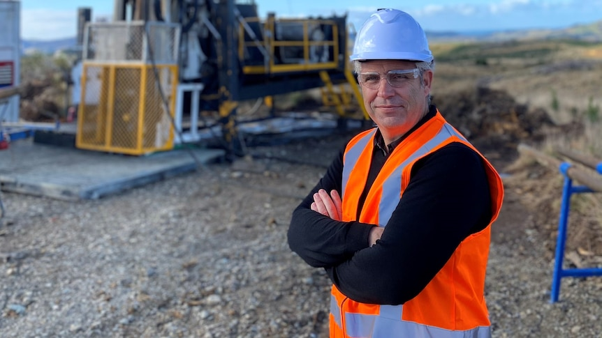 Mr House stands in front of a piece of mining equipment, wearing a high vis vest and helmet.