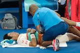 Tennis player receives medical treatment on court at the Australian Open.