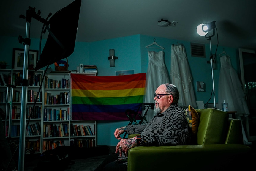 Geoffrey Ostling sit in his room in front of a rainbow flag, books line one wall, while wedding dresses hang on another.