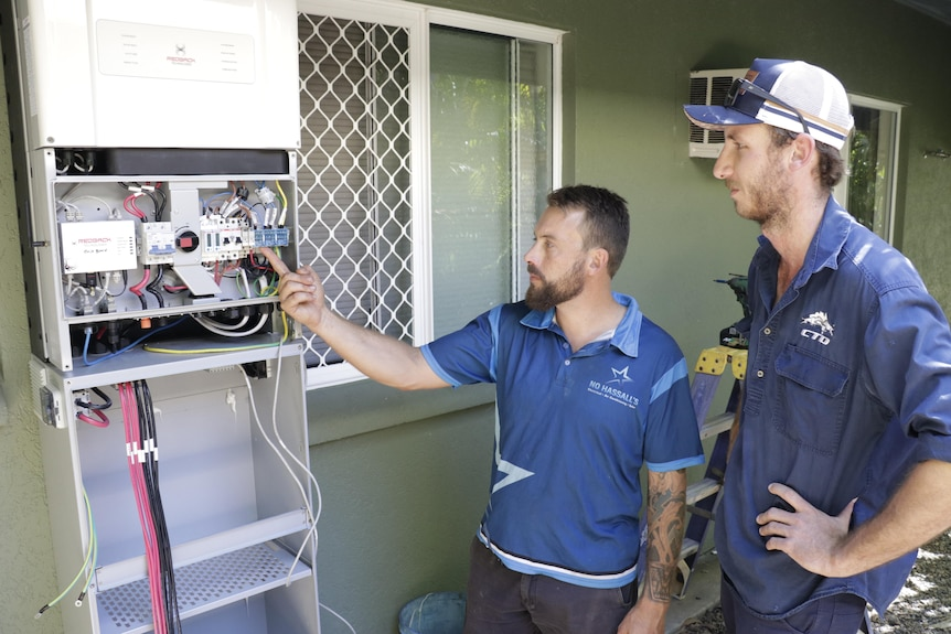 two men in tradesmen clothing with a household battery