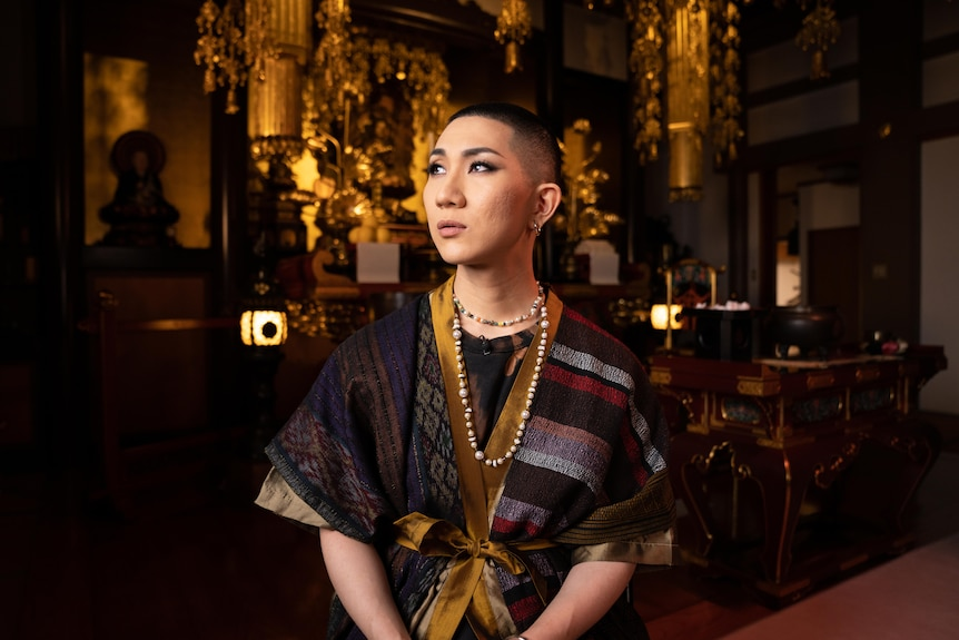 A young Japanese monk with heavy eye make up looking to the heavens.