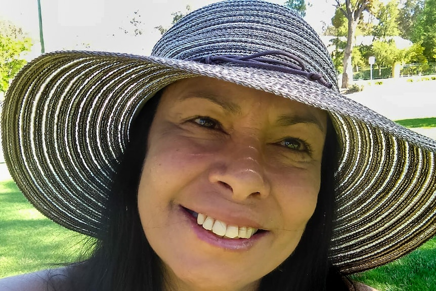 Woman wearing wide brim hat smiles looking at camera with park in background.