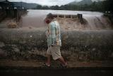 A man walks on a bridge over a river during tropical storm Amanda.