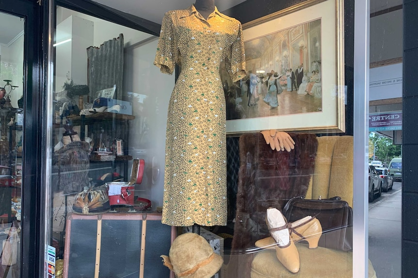 Old style shopfront of vintage shop displaying dresses, hats, gloves, shoes, fur and old suitases