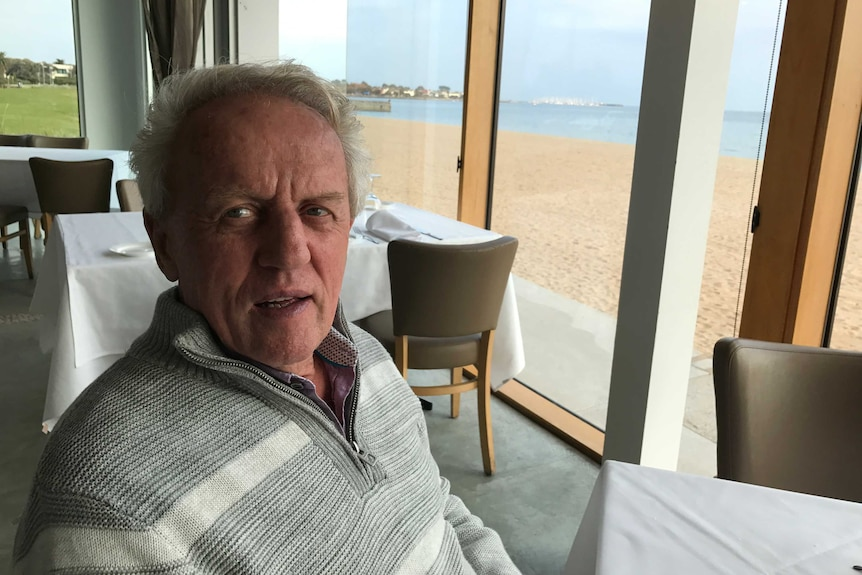 Conrad Whitlock sits at a table in a restaurant. The beach is visible through the window behind him.