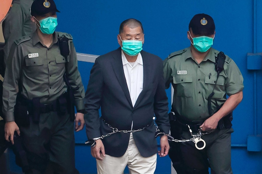 A man wearing a suit and mask is escorted in chains by two uniformed police wearing black caps and masks