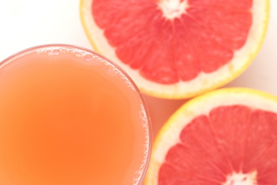 A glass of grapefruit juice and some cut fruit.