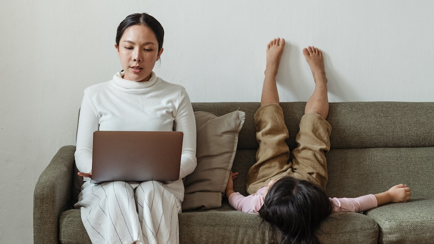 Woman sitting on a couch working with laptop while child puts feet on the wall
