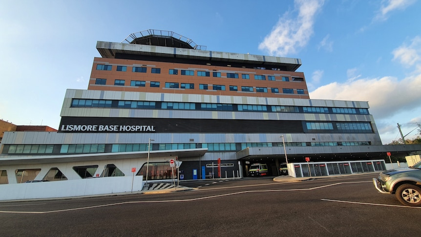 The exterior of a hospital with a helipad on top of a multistorey building and ambulances parked at street level.