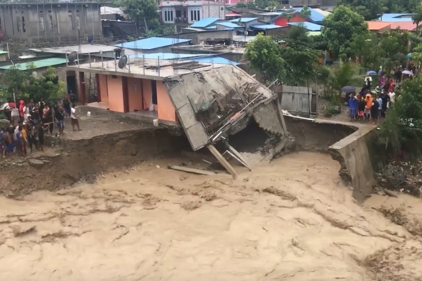 water washes away part of a house as it runs through Dili