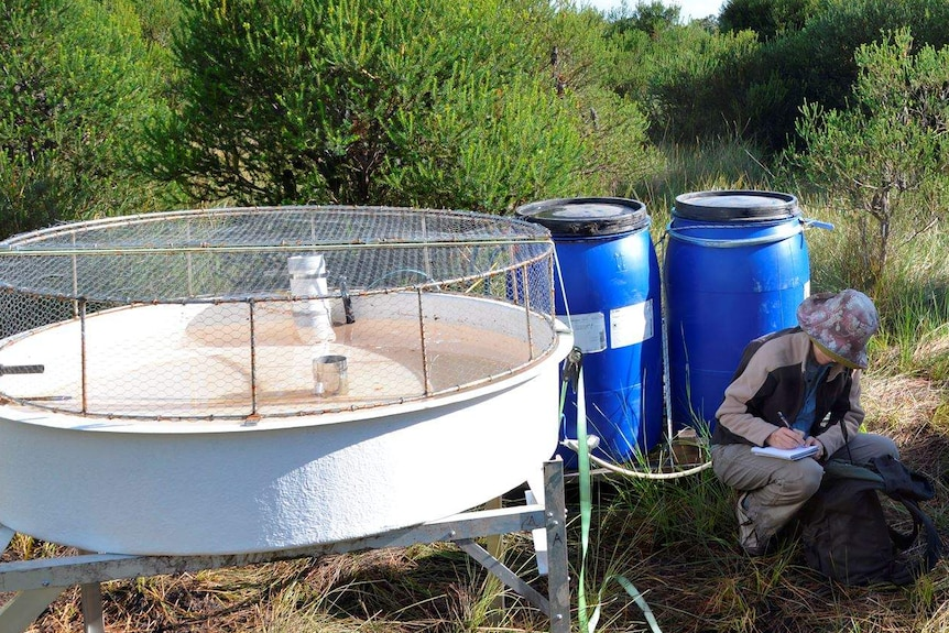 A woman crouches next to large drums and other scientific devices in bushland, taking notes.