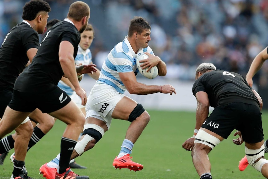 an Argentine player runs with the ball past All Blacks players