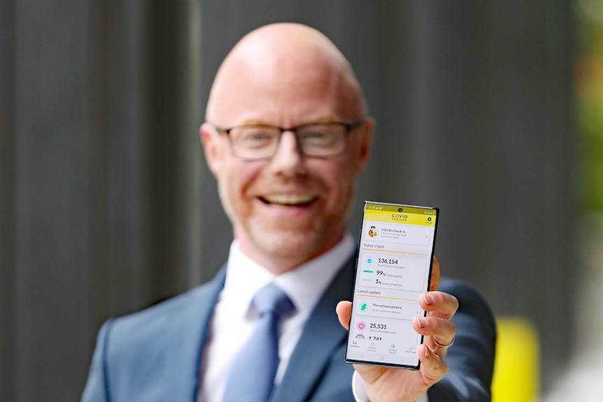 A man holding a smartphone displaying the COVID Tracker App.