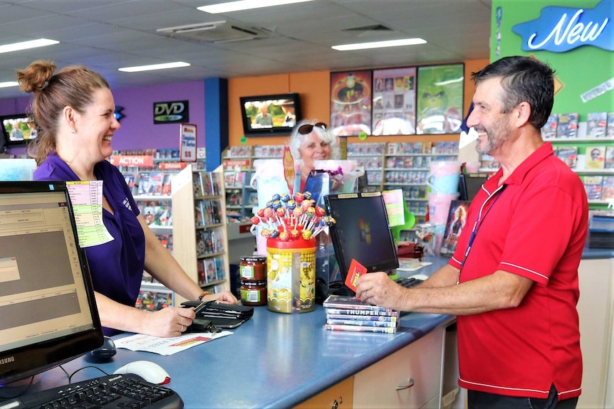 Manager and customer smiling at each other across the counter at a video store.