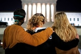 Three women stand with their arms around each other looking towards the Supreme Court, lit up in the night.