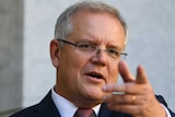 Scott Morrison stands at a podium in a courtyard and points into the distance