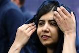 Malala Yousafzai adjusts a blue headscarf.