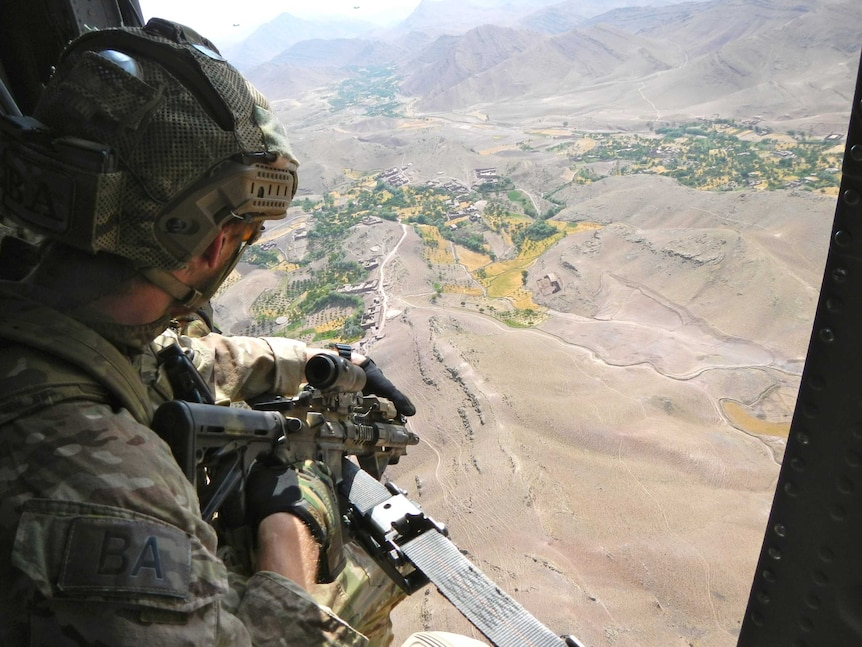 A soldier wearing a camouflage while holding a gun looks out the side of a helicopter on a brown mountainous area