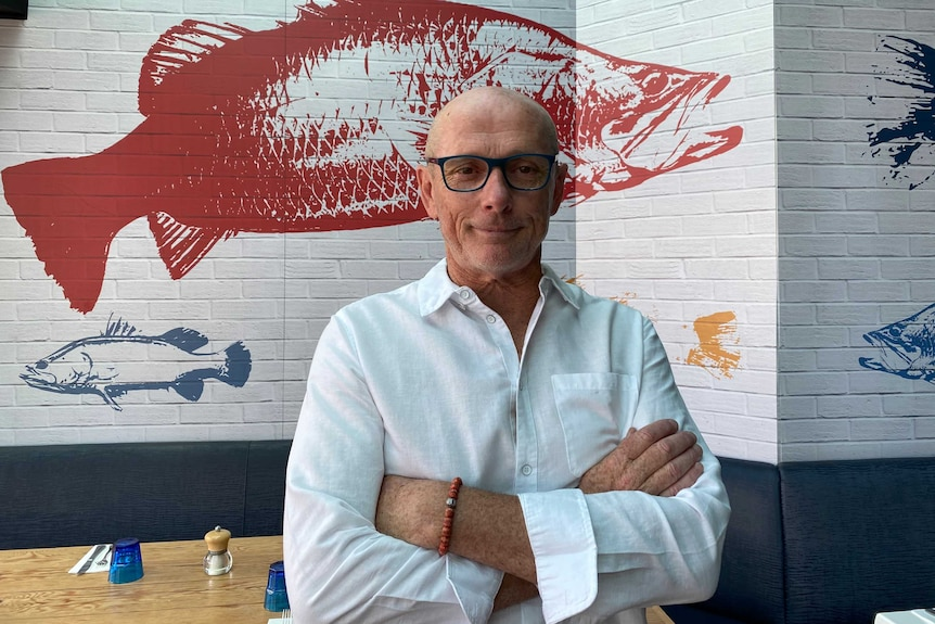 A bald white man is wearing a white shirt, arms folded is in his restaurant. A giant red fish is painted on the wall behind him.
