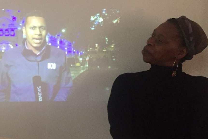 Woman looking sideways at image projected on wall of reporter holding ABC News microphone.