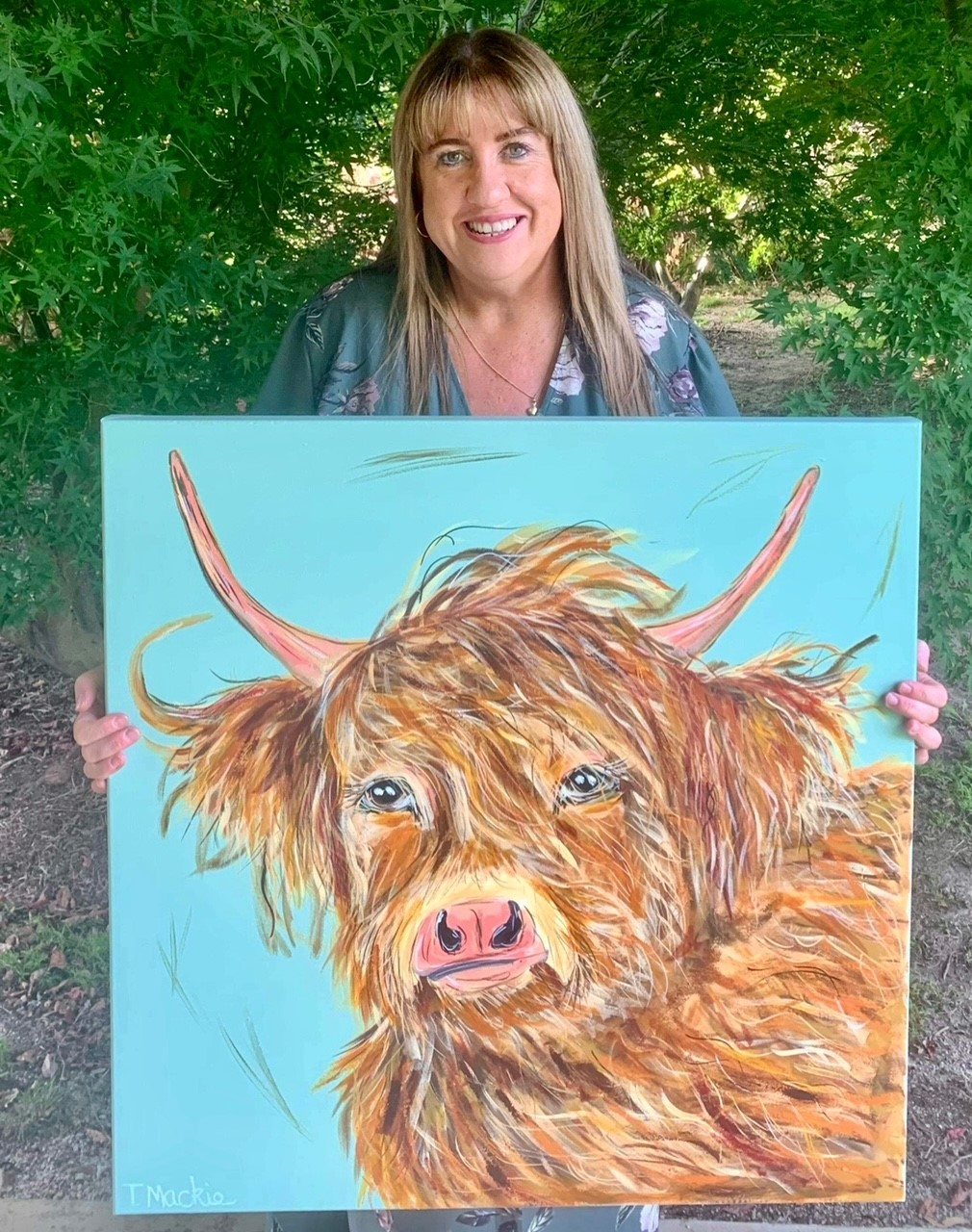 Picture of Tracey Mackie holding painting of Cow titled Catriona
