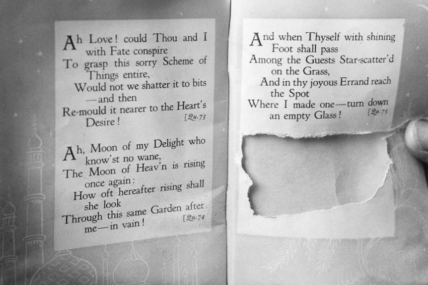 A black and white photo of a book with a section torn out.