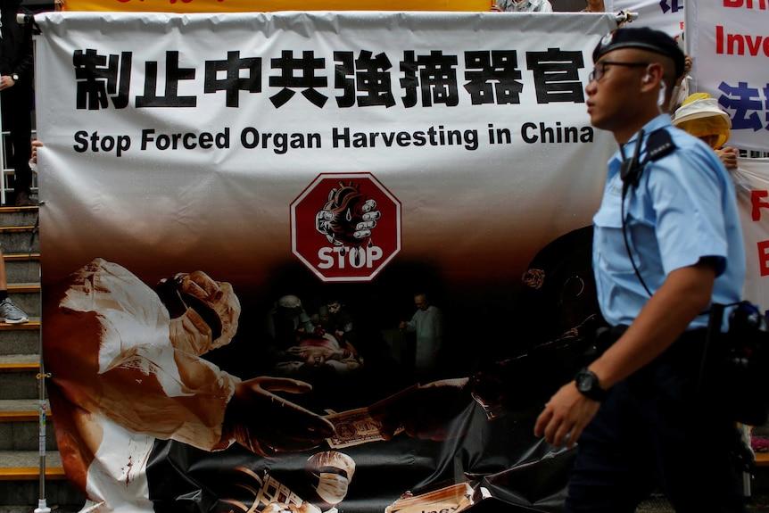 """在香港,一个法轮功抗议横幅上写着""""制止中共强摘器官""""。"""